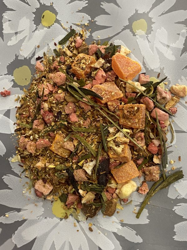 Green Tea leaves displayed with pieces of fruit including strawberry, lemon, orange, and papaya.